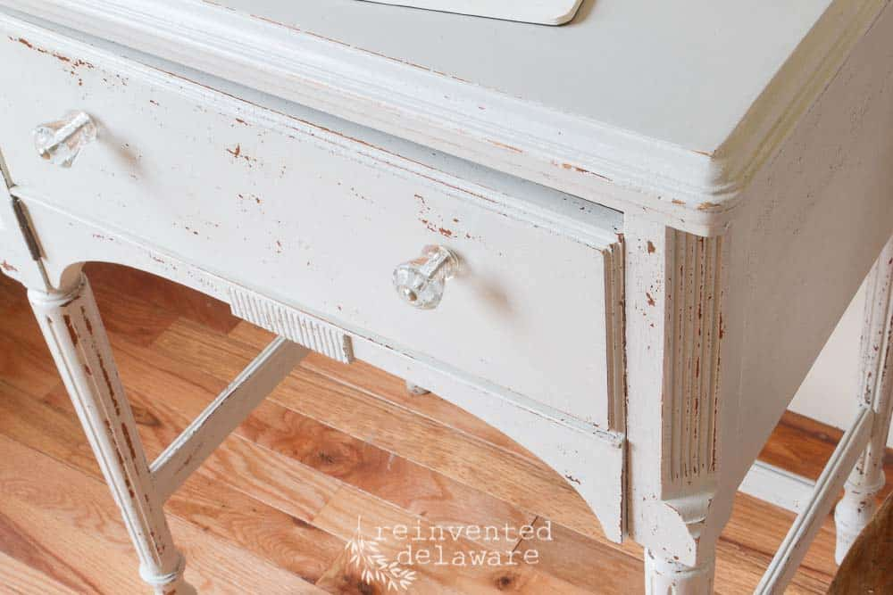 top view of sewing cabinet showing glass drawer pulls and chipping paint