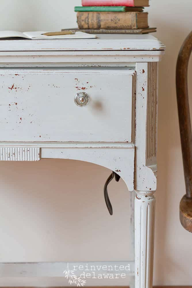 close up front view of sewing cabinet with chipping paint