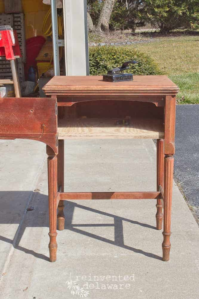 vintage sewing cabinet in original finish with cabinet door open showing the additional shelf