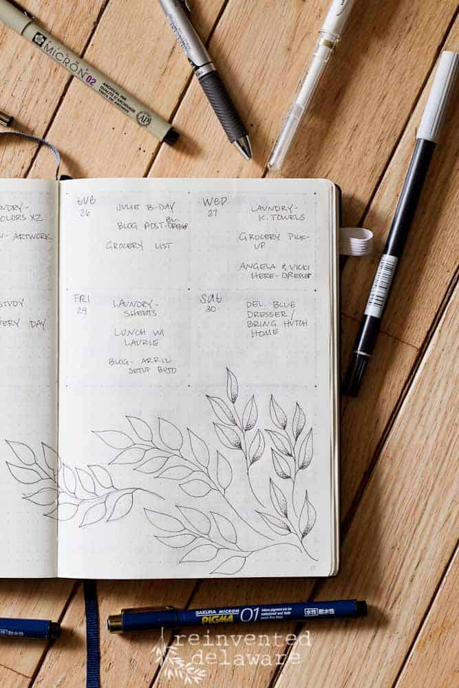 weekly layout page in bullet journal with various pens and leaf doodles on page