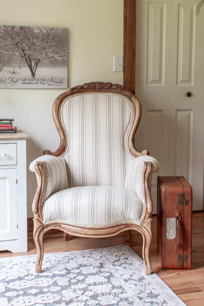 finished victorian chair after completing the steps to reupholster a chair tutorial. Chair is staged next to a pianted antique washstand and a vintage suitcase sitting next to it. Well decor is hanging behind