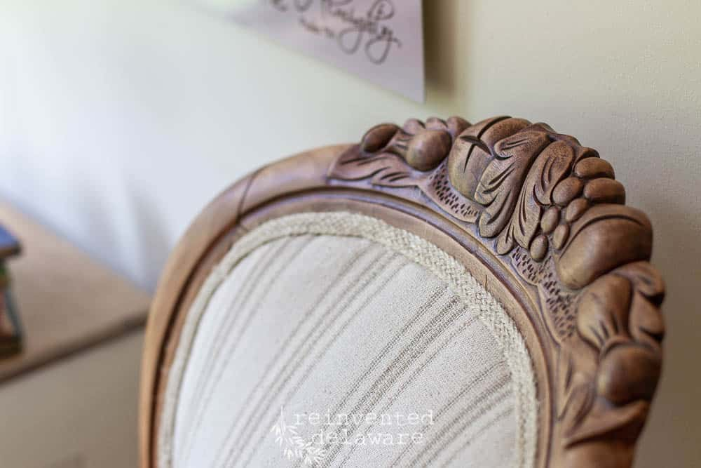 carved detail of wood on the back of a reupholstered chair that it Victorian style