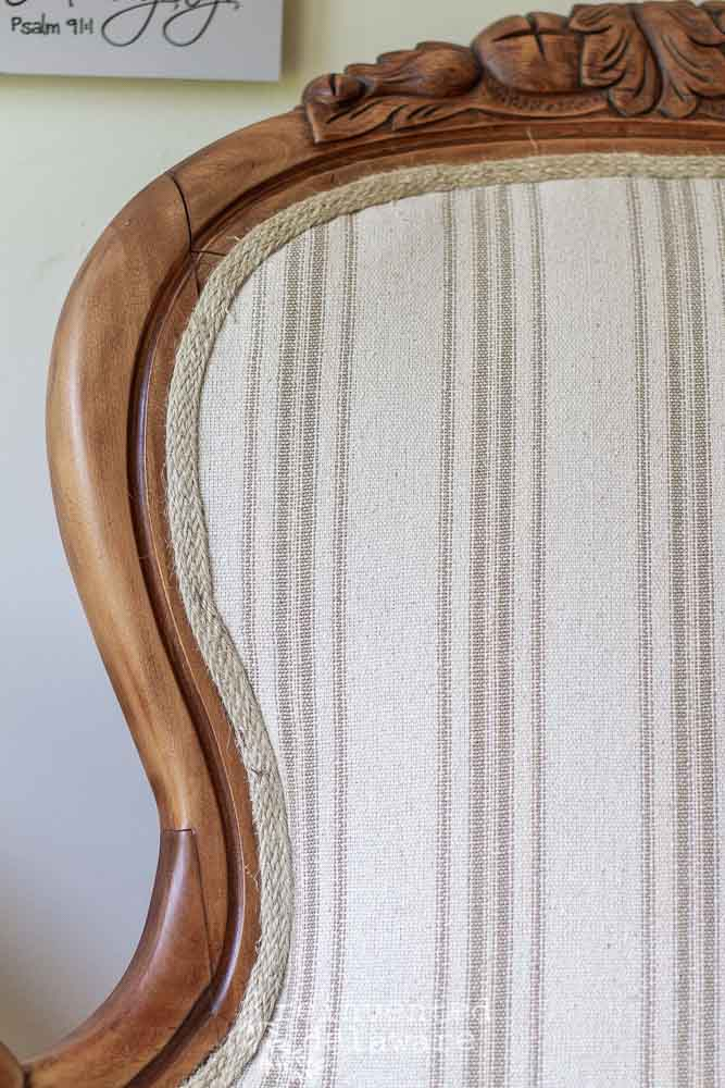 close up of carved wood on Victorian chair that has bee reupholstered with grainsack style fabric