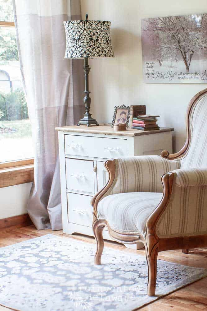 side view of reupholstered Victorian chair staged with a painted washstand that has knick-knack sitting on top with a lamp, wall decor hanging behind the chair, gray rug on the floor