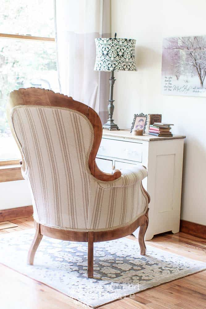 back view of Victorian chair that has been reupholstered in reproduction grainsack fabric in neutral colors. The chair is sitting on a gray rug and in front of a painted antque washstand with knick-knacks and a lamp. Wall decor is hanging on the wall