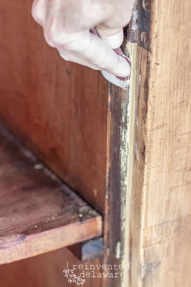 sanding off extra paint on antique pine cupboard