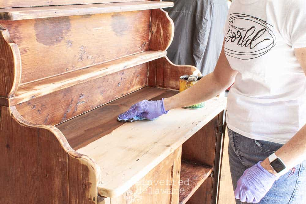 staining top of antique pine cupboard with General Finishes Van Dyke Brown Glaze
