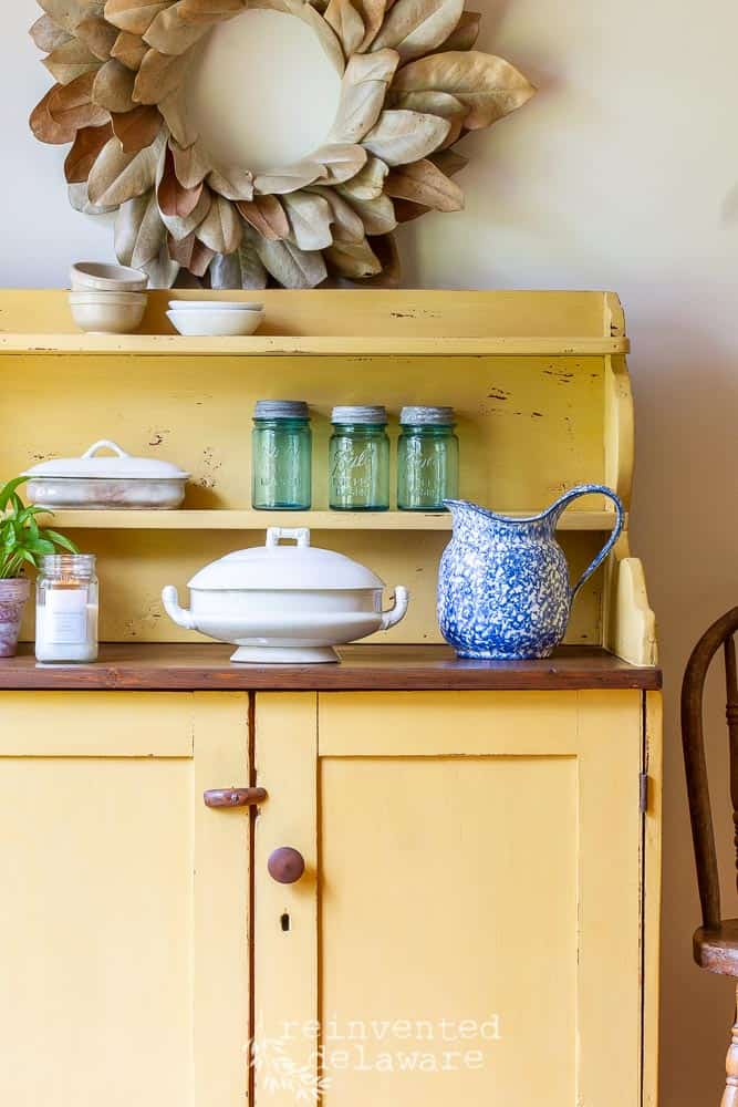 close up of painted vintage antique pine cupboard with dishes on top