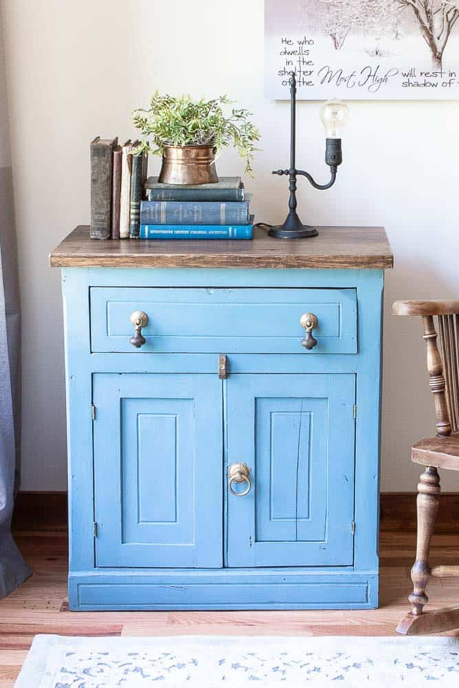 finished and staged washstand with vintage books, lamp and plant on top. Washstand finished in Miss Mustard Seed Milk Paint in French Enamel Blue