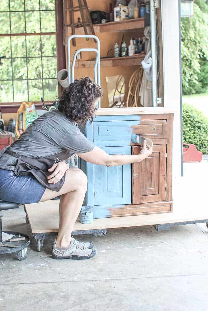 lady showing how to apply milk paint on a washstand