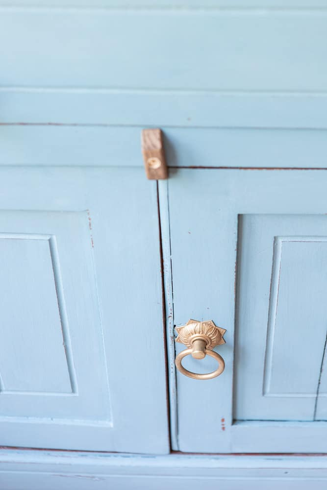 detail shot of closure and antique hardware on door of washstand that was made over with milk paint applied