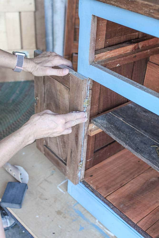 lady showing how to clean paint from edges of frame on washstand