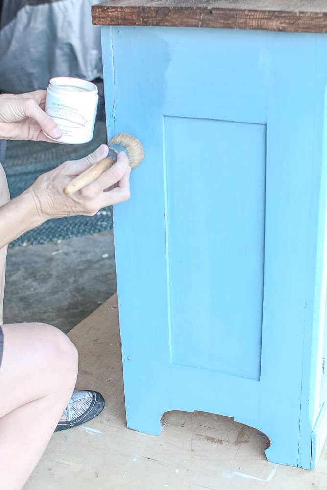lady sealing milk paint finish on a washstand painted in Miss Mustard Seed milk paint in French Enamel Blue