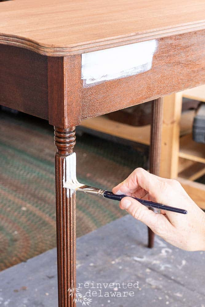 fluted table leg being painted with an artist's paintbrush