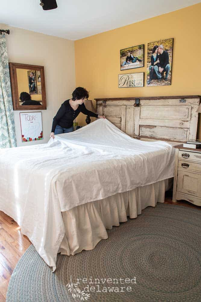 cotton sheets being put on the bed by a lady