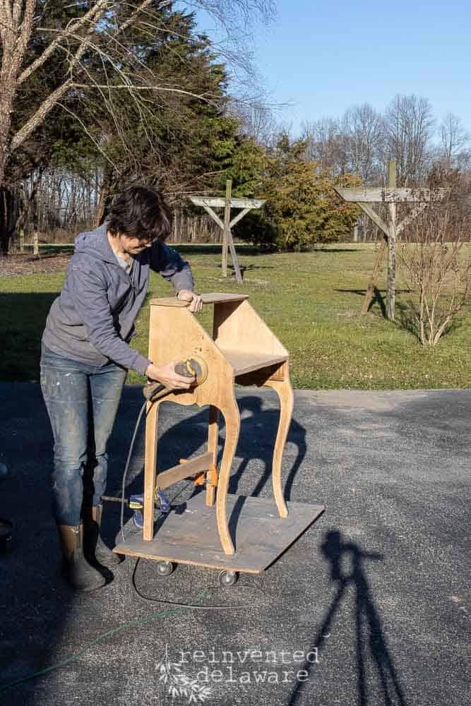 antique oak fold down desk being sanded to bare wood