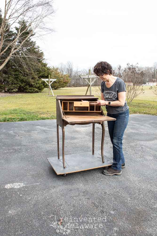 lady disassembling the organizer from an antique fold down secretary desk
