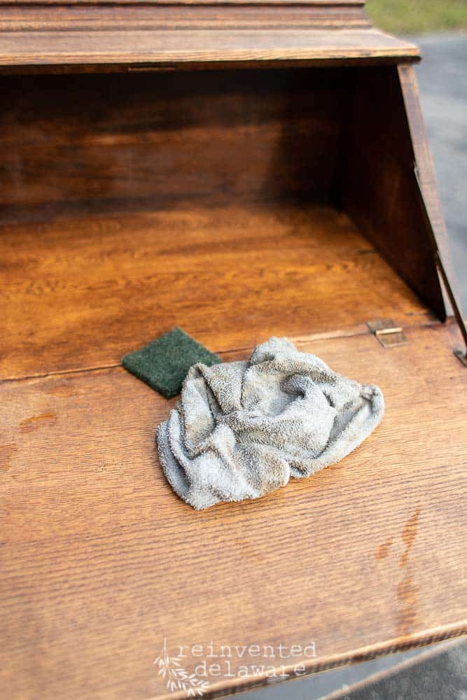 cleaning cloths on an antique fold down secretary desk
