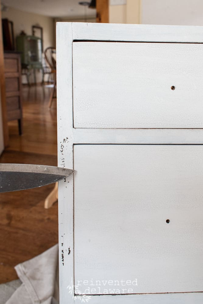 using flat edge knife to distress painted furniture