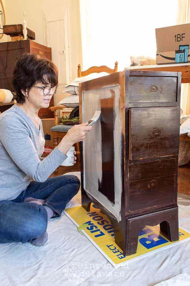lady painting small desk cabinet using miss mustard seed milk paint