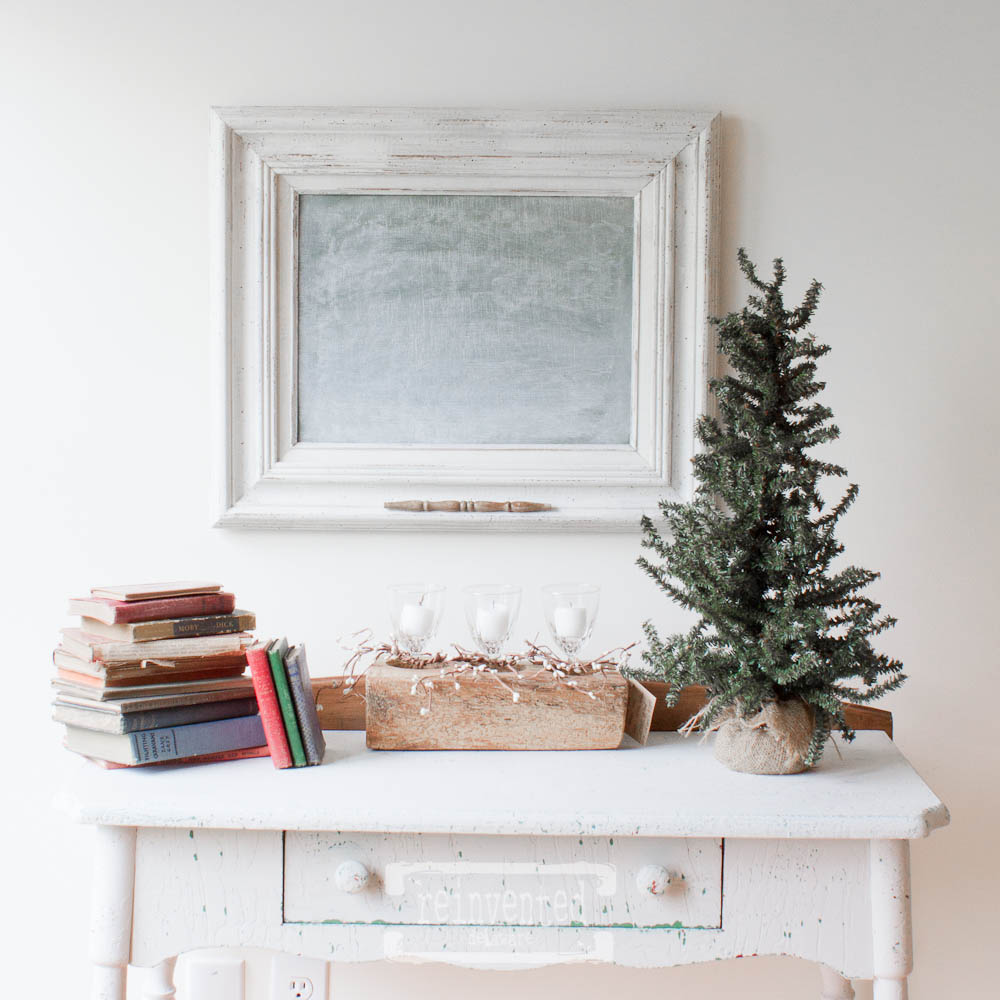 upcycled framed chalkboard with spindle chalk holder handing above desk with books, candles and small Christmas tree