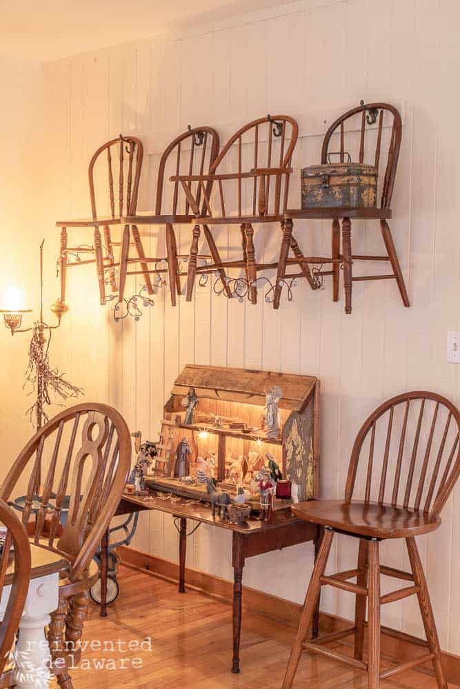 dining room with nativity scene and children's antique chairs hanging on wall