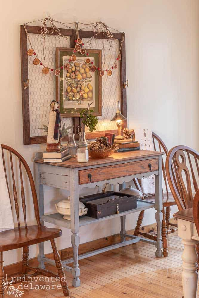 dining room buffett with Christmas decor on top and hanging orange slice garland on wall decor