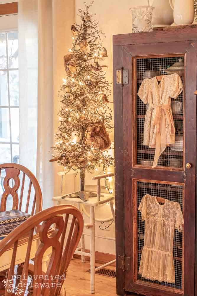 small decorated Christmas tree sitting on top of vintage highchair next to a large antique storage cabinet