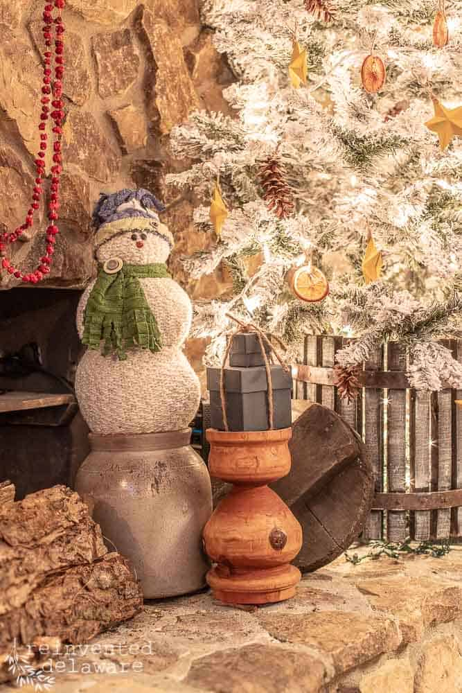 fireplace hearth with handmade snowman and painted gift boxes near flocked Christmas tree