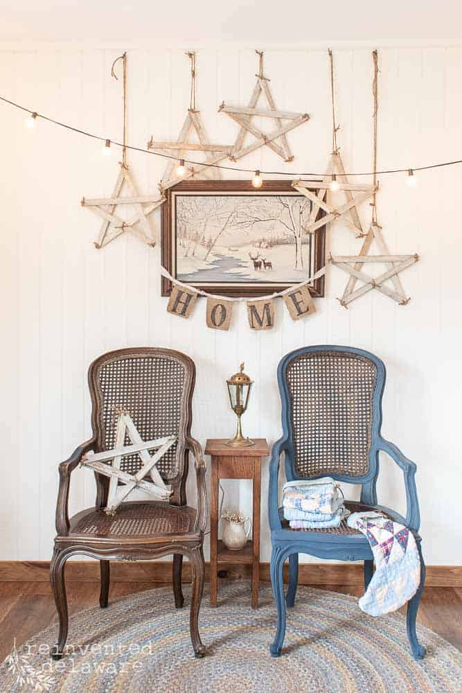 two wicker chairs, one painting, 'home' wall banner and five hanging handmade stars vignette