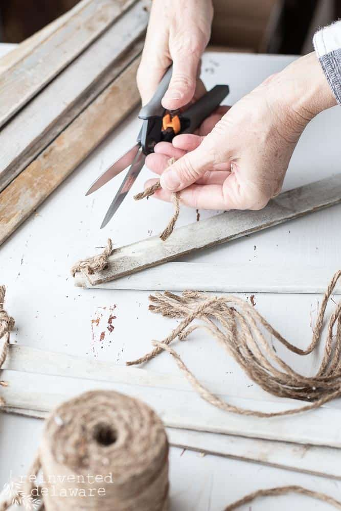 demonstration of tying jute on handmade farmhouse style stars to hold them together in the star shape and then cutting the twine shorter