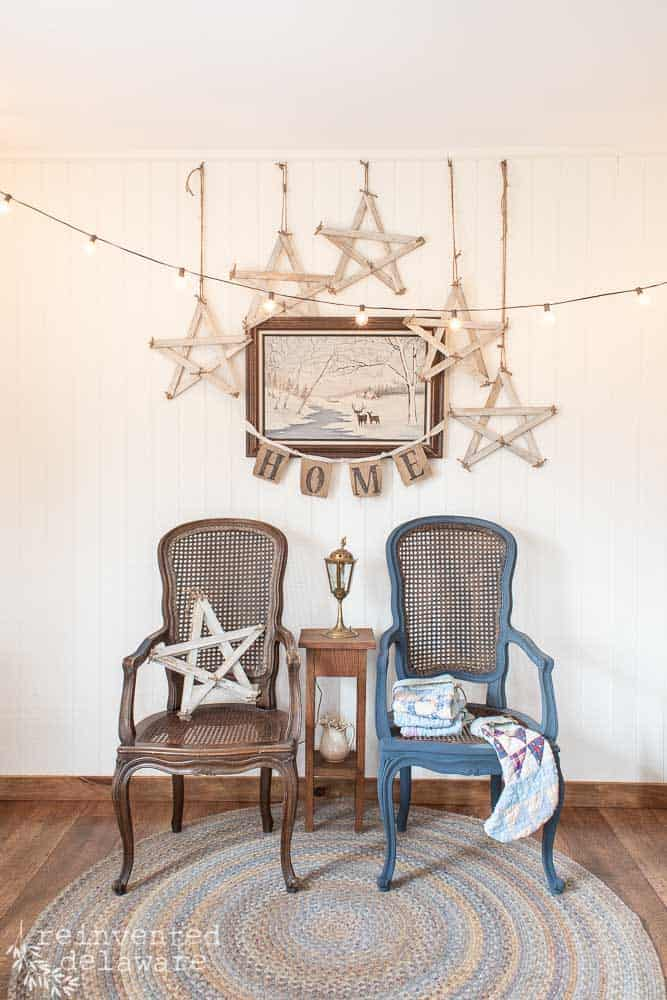 two wicker chairs with handmade farmhouse style stars hanging above them and around a painting