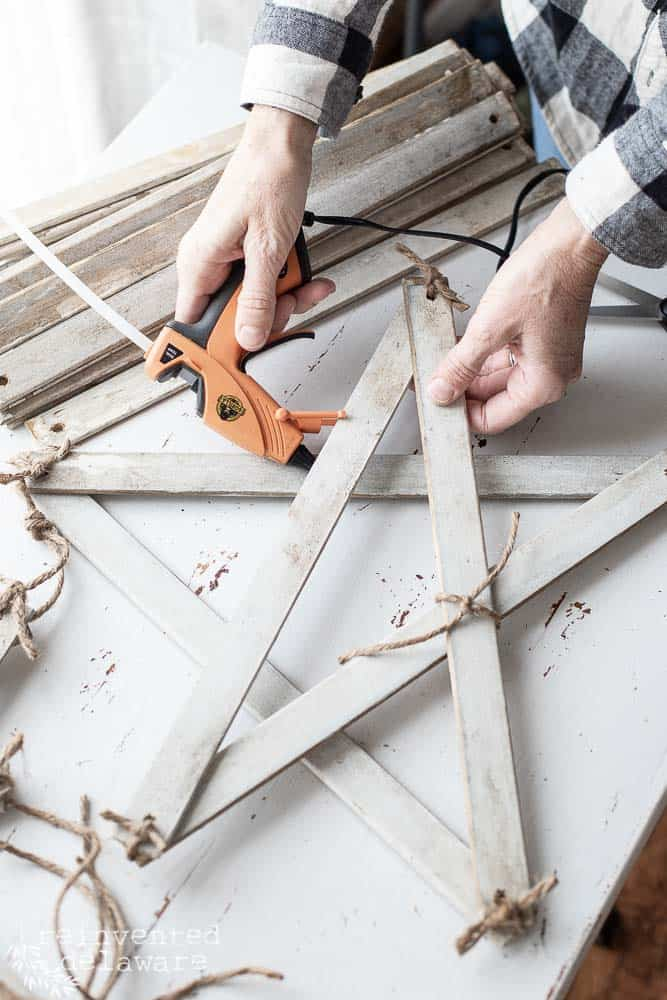 using hot glue to secure intersections of the handmade farmhouse style star