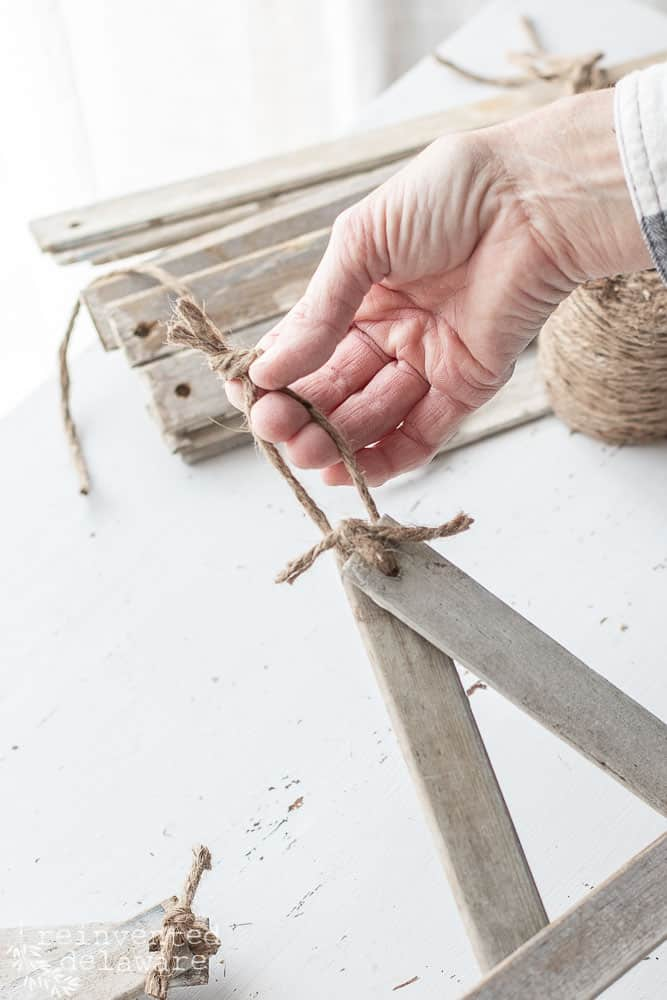 close up of jute twine being tied on farmhouse style star for hanging