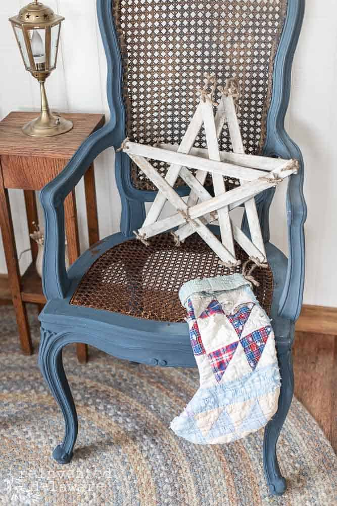 wicker chair with two stacked handmade farmhouse style stars sitting on chair and quilted Christmas stocking on the side of chair