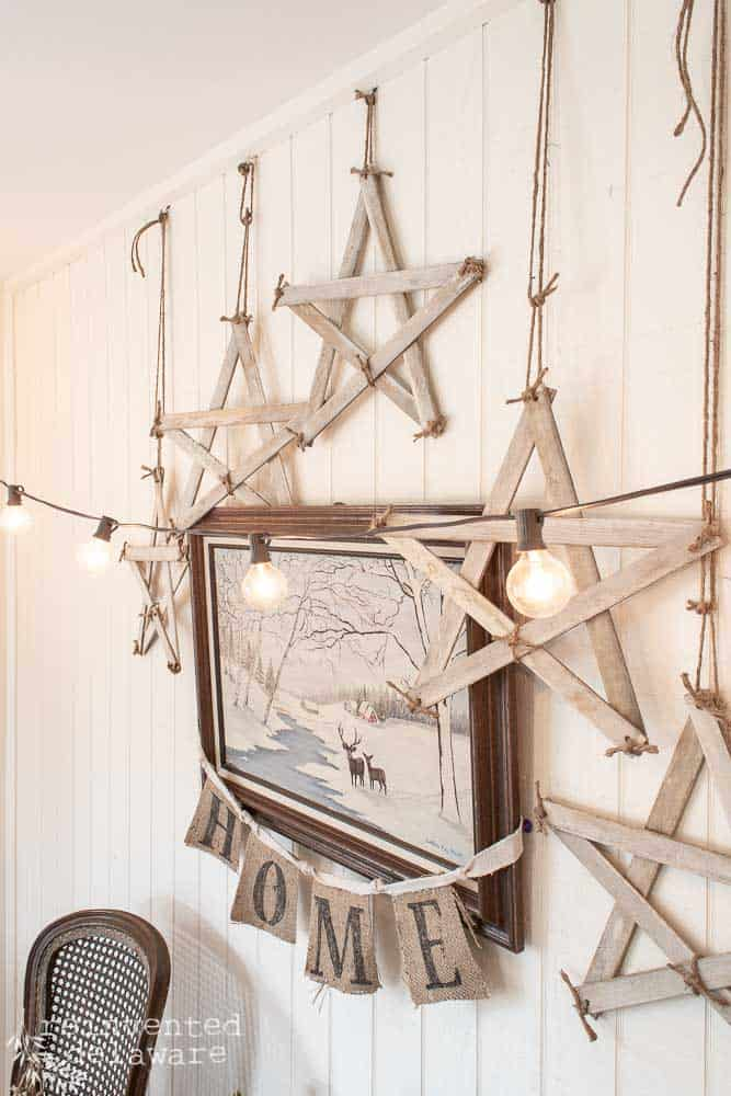 handmade farmhouse style stars hanging on a wall around a painting