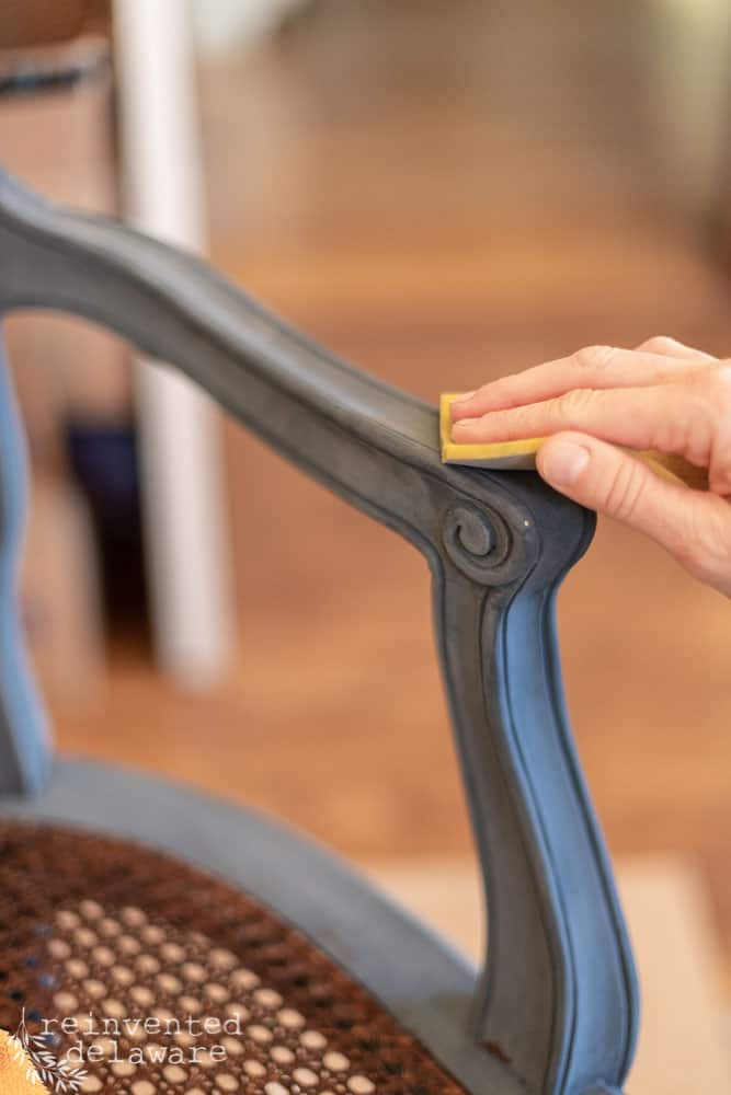 close up of painted framing on caned chair being sanded smooth