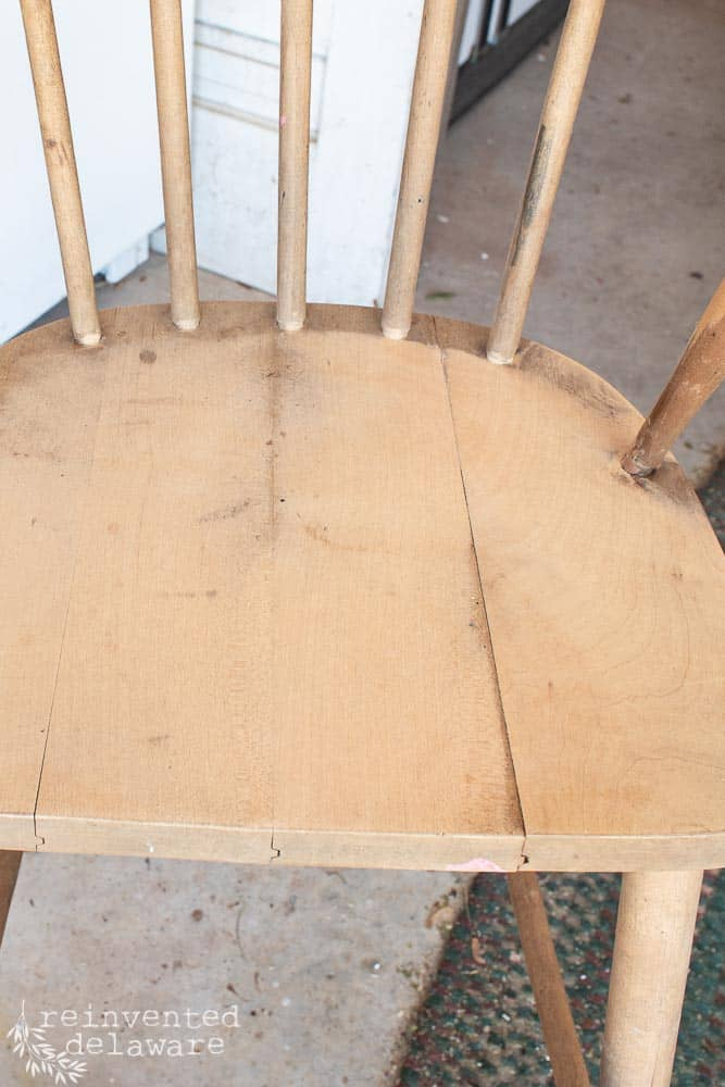 close up of loose boards on broken chair seat of a youth chair