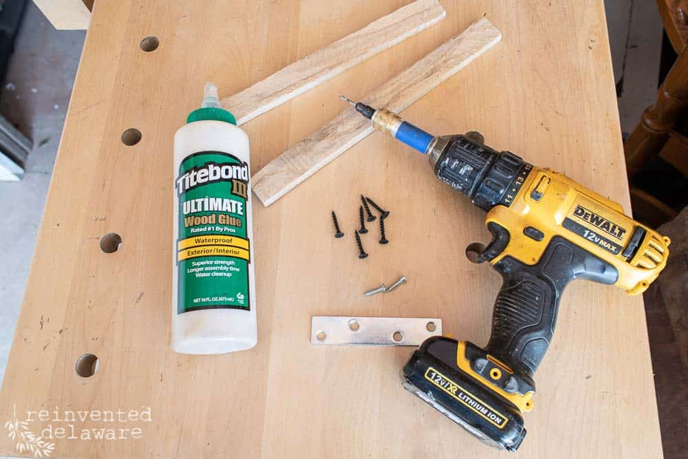 power drill, bottle of wood glue, scraps of wood for mending bracket, screws, counter-sink drill bit all laying on top of workbench