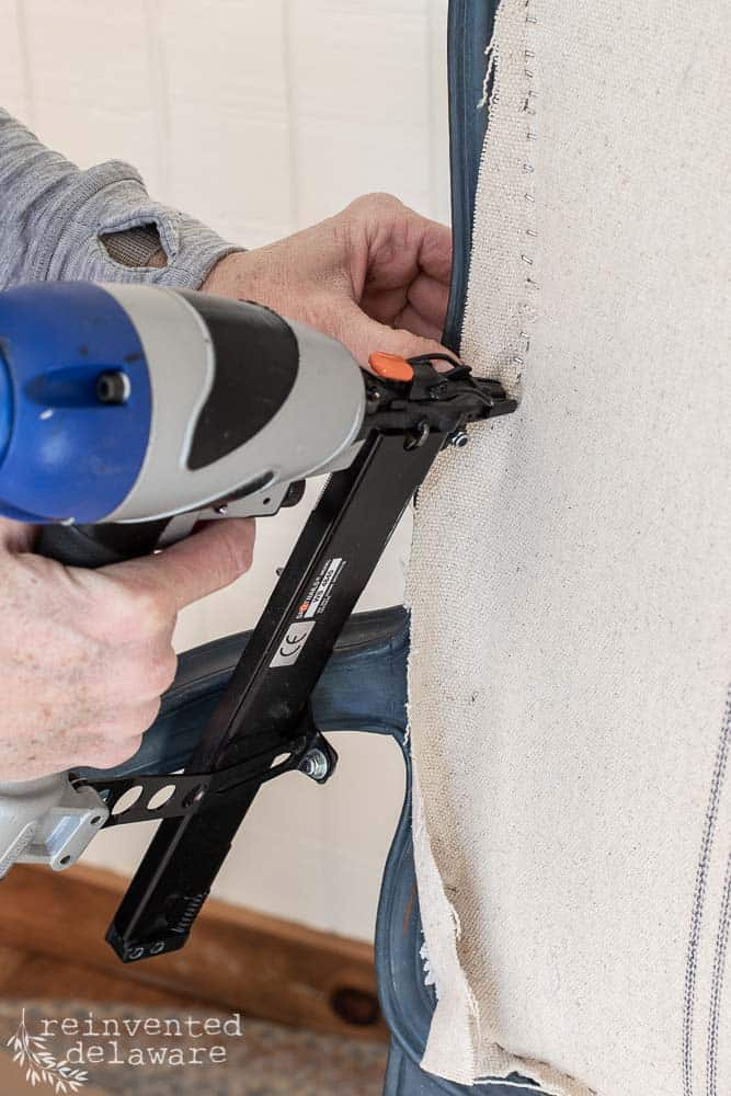 using pneumatic staple gun to attach upholstery fabric to caned chair. furniture makeover ideas