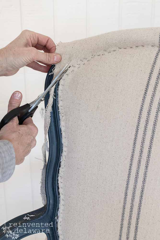 cutting off excess fabric after stapling onto back of caned chair. furniture makeover ideas