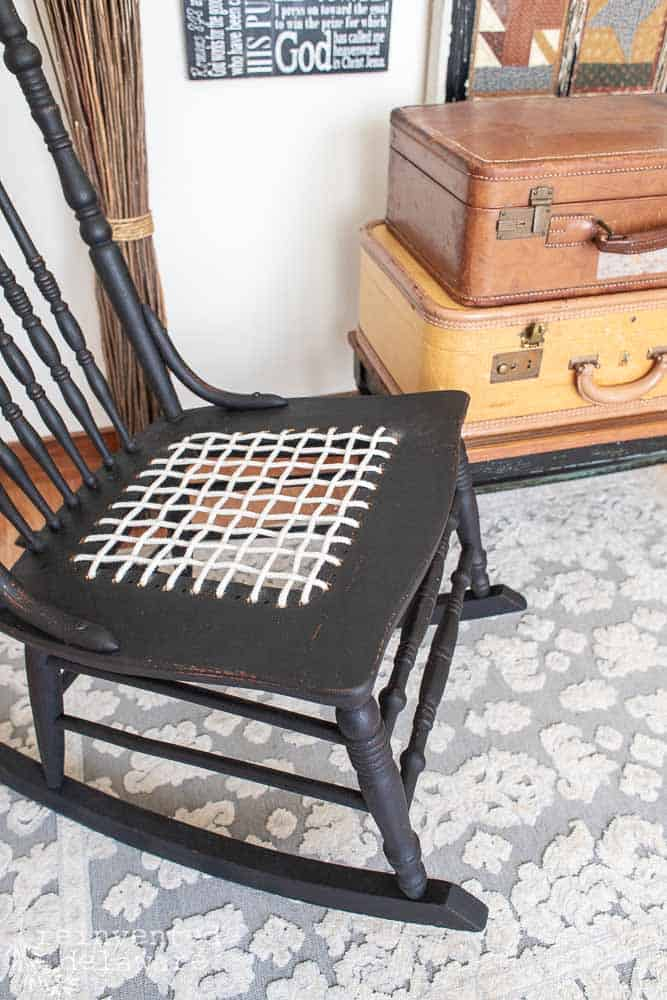 finished black rocker with repair 'caned' seat using clothesline rope close up shot of seat area