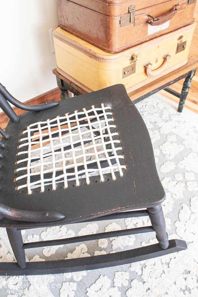 finished black rocker with repair 'caned' seat using clothesline rope close up of seat area