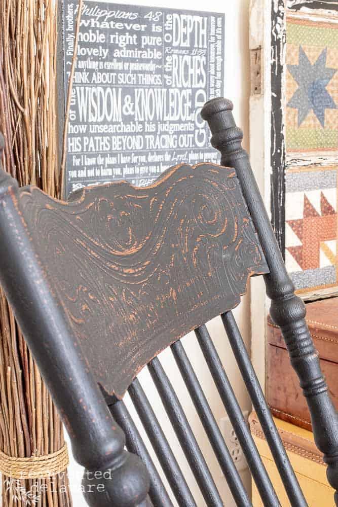 finished black rocker showing carved detail on back of chair