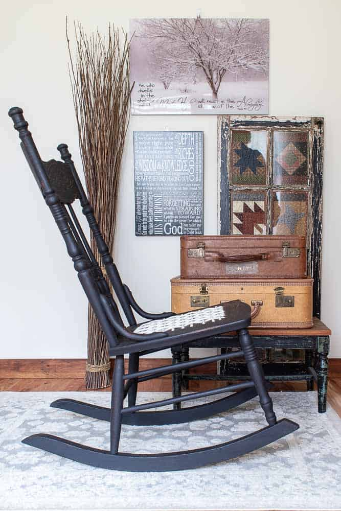 side view of repair antique oak rocker painted in black milk paint with stack of vintage suitcases as side table and wall decor