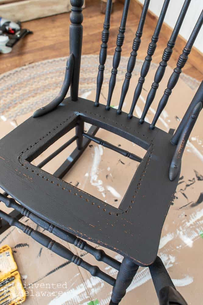 antique black oak rocker with missing caning in seat area