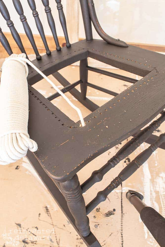 black oak rocker with missing caned seat with clothesline rope laying on top