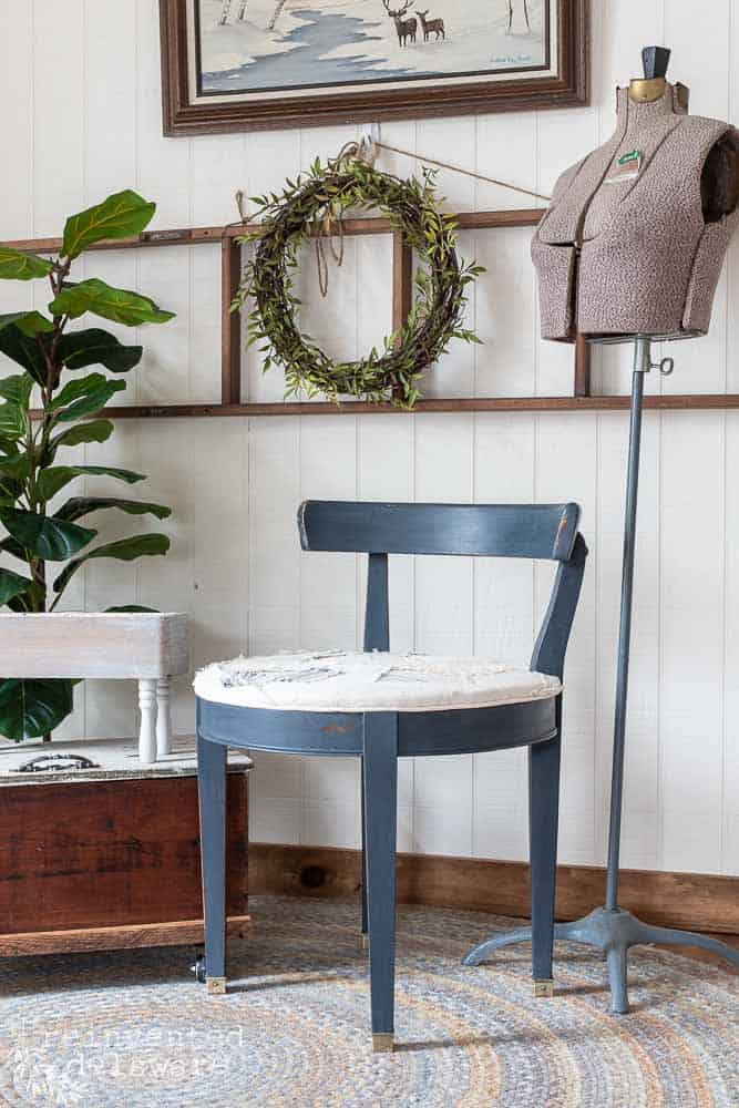 staged vanity chair with vintage dress form, wooden toolbox on wheels and plants