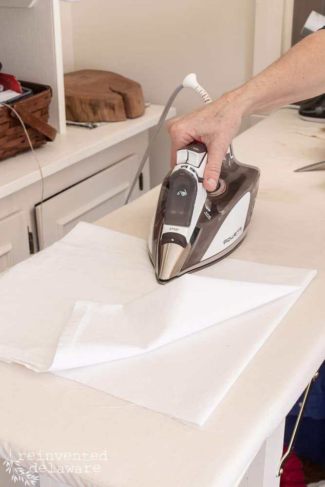 woman ironing fabric for chair makeover ideas