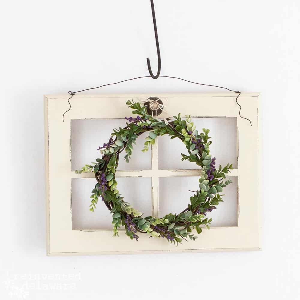 upcycled window with greenery wreath hanging on it